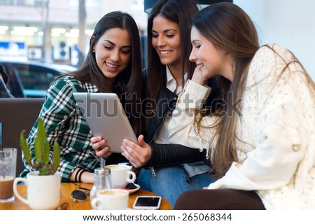 Portrait of three young woman using digital tablet at cafe shop. - stock photo