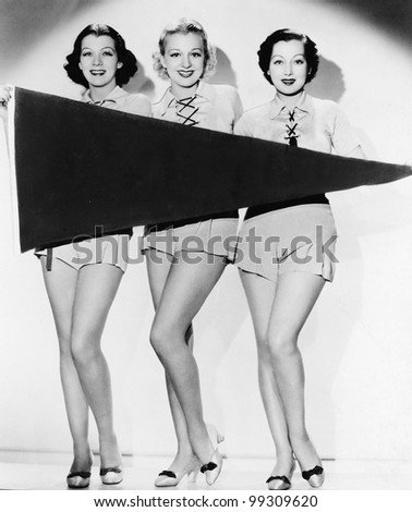 Portrait of three young women holding a banner and smiling - stock photo