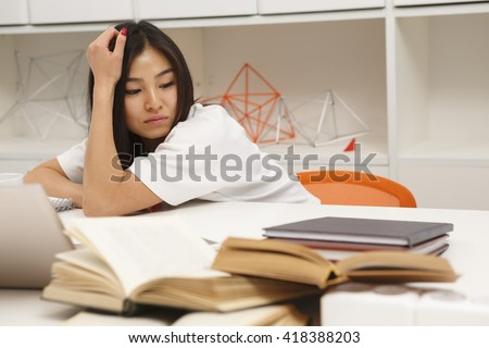 Portrait of tired Asian student resting and relaxing after hard-working day in library. Happy brunette lady looking on exercise-books.