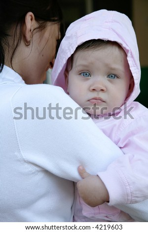 portrait of tired baby being held by mother