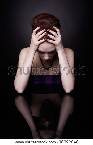 portrait of tired beautiful young woman sitting at dark mirror surface holding her head with hands - stock photo
