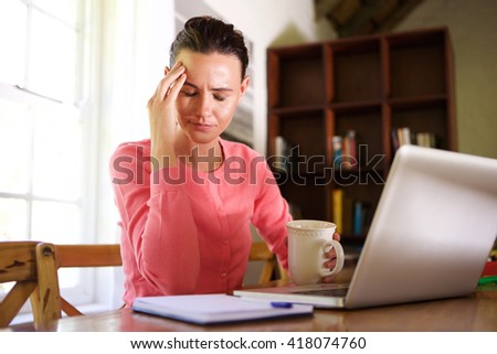Portrait of tired business woman with headache while working at home - stock photo