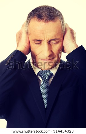 Portrait of tired businessman covering ears with hands.