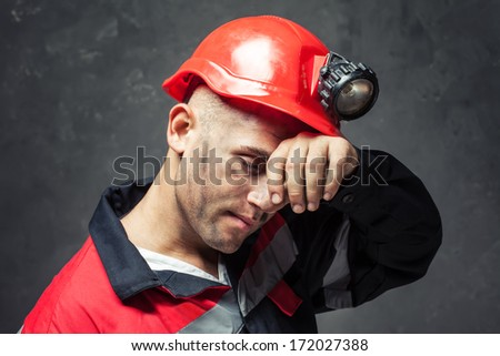 Portrait of tired coal miner wiping forehead his hand against a dark background - stock photo
