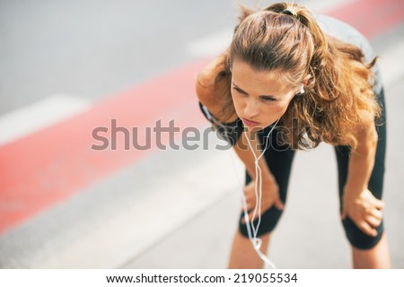 Portrait of tired fitness young woman outdoors in the city catching breathe - stock photo
