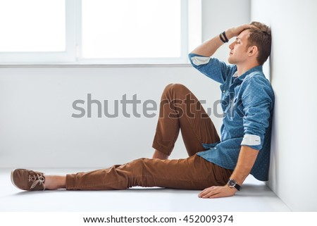 Portrait of tired handsome man sitting on the floor in studio