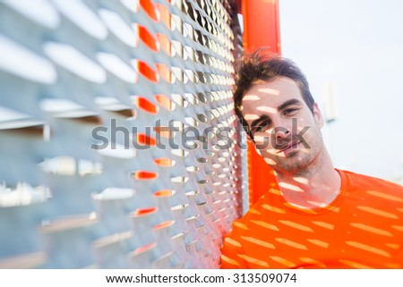 Portrait of tired male runner leaning on metal fence thoughtful looking to the camera, young caucasian sport build man taking break after active training outdoors with copy space area for text message - stock photo