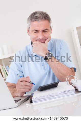 Portrait Of Tired Mature Man Doing Finances