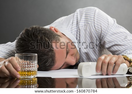 Portrait of tired overwhelmed young man sleeping at work with glass of alcohol on desk.
