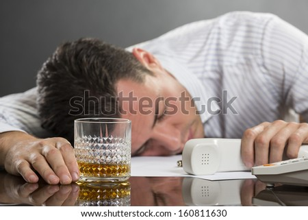 Portrait of tired overwhelmed young man sleeping at work with glass of alcohol on desk. Selective focus on the glass. - stock photo