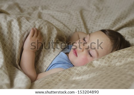 Portrait of toddler child,  boy or girl, sleeping under a blanket in a bed.  - stock photo