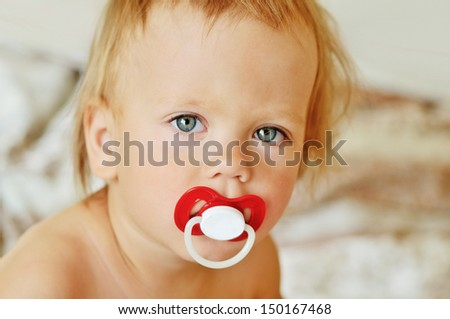 portrait of toddler with dummy - stock photo