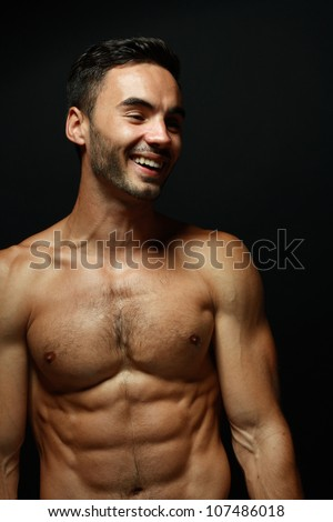 portrait of topless athletic smiling macho man posing over black background - stock photo