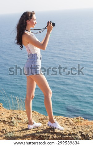 Portrait of tourist happy smiling girl making photos of the nature and sea views by old camera on the peak of mountain over sea background - stock photo
