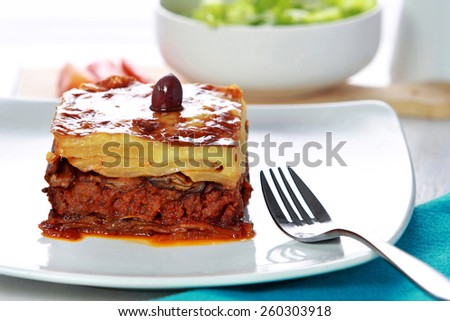 portrait of Traditional Greek beef Moussaka with olive served in dish with fork aside - stock photo