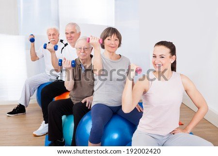 Portrait of trainer and senior customers using hand weights while sitting on fitness balls at gym - stock photo