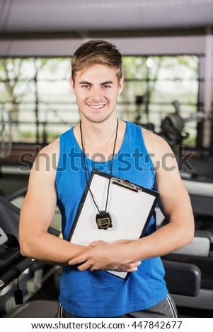 Portrait of trainer standing in gym with clipboard and stopwatch