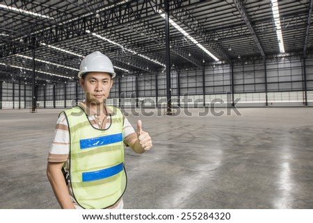 Portrait of tramsportation engineer standing at Large modern empty warehouse - stock photo