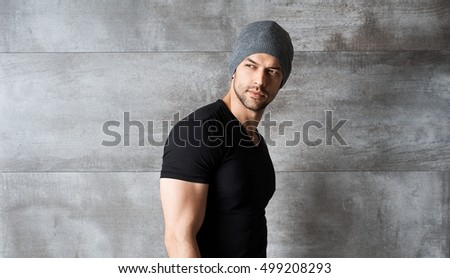 Portrait of trendy athletic young man in cap leaning against concrete wall.