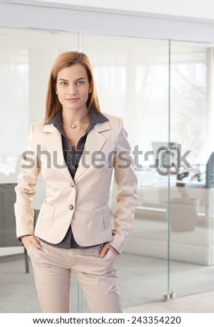 Portrait of trendy businesswoman at office, smiling with hands in pockets. - stock photo