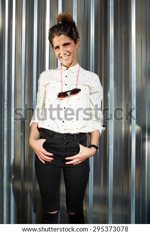 Portrait of trendy female hipster dressed in black pants, elegant shirt and sunglasses hanging around her neck standing against shiny chrome background with copy space for your text message or content - stock photo