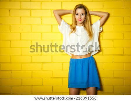 Portrait of Trendy Hipster Girl with Hands behind Head on Yellow Brick Wall Background. Urban Fashion Concept. Copy Space. - stock photo