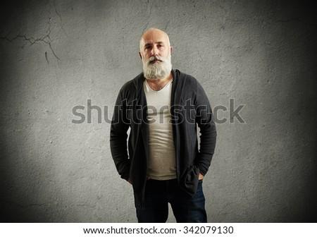 portrait of trendy senior man over dark grey wall - stock photo