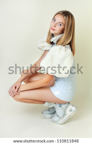 Portrait of trendy teen girl in miniskirt and leather dress sitting against white background