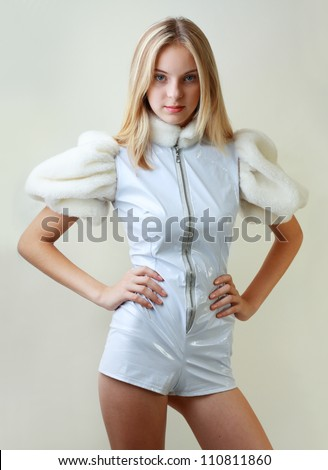 Portrait of trendy teen girl in miniskirt and leather dress standing against white background