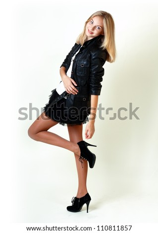 Portrait of trendy teen girl in miniskirt and leather jacket smiling against white background