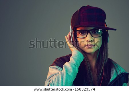 Portrait of trendy woman listening to music on headphones hiphop fashion - stock photo