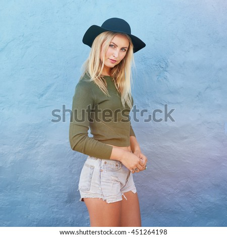 Portrait of trendy young female wearing casual clothes posing over blue background. Attractive young caucasian female model standing in front of a blue wall and looking at camera. - stock photo