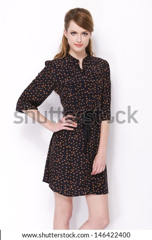 portrait of trendy young woman in black dress posing on white background - stock photo