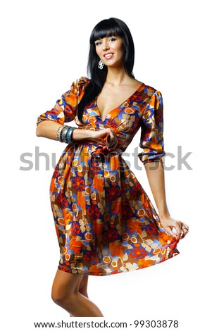 Portrait of trendy young woman in funky orange dress smiling against white background - stock photo