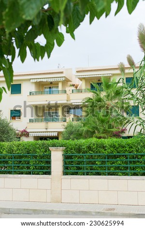 Portrait of tropical apartment building with fence. - stock photo