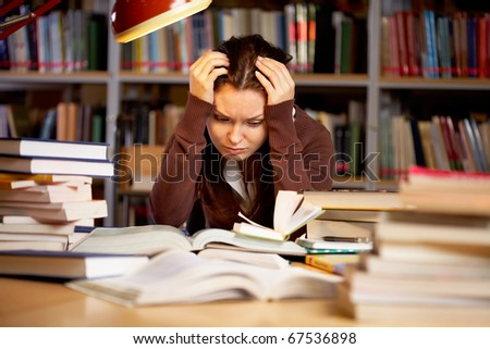 Portrait of troubled girl touching head while preparing for seminar in college library - stock photo