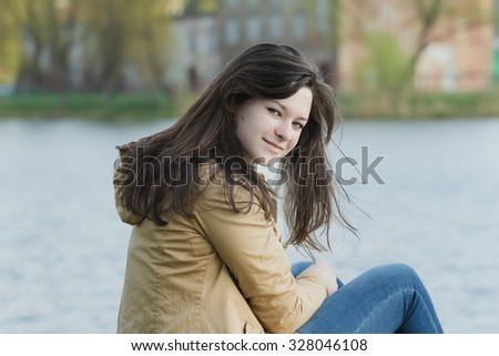 Portrait of turning around student girl is wearing beige demi-season jacket at city park lake background - stock photo