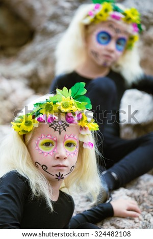 Portrait of twins with black clothing and sugar skull makeup - stock photo