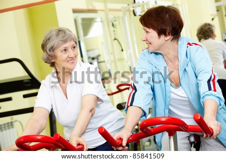 Portrait of two active seniors sitting on exercise bicycles - stock photo