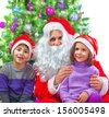 Portrait of two adorable kids sitting with Santa Claus at home near Christmas tree, winter holidays, New Year party, festive decorations, fun concept - stock photo