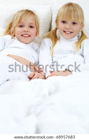 Portrait of two adorable sisters lying in the bed