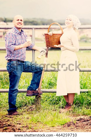 Portrait of two adult farm workers taking a pause and holding glass with fresh milk next to field fence