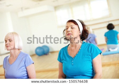 Portrait of two aged females relaxing in sport gym  - stock photo