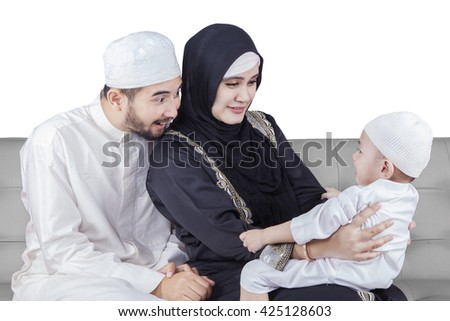 Portrait of two Arabic parents sitting on the sofa while playing with their son