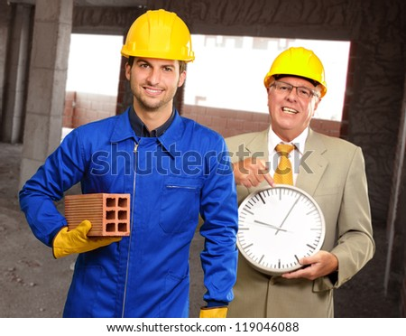 Portrait Of Two Architect Engineers Holding Clock And Brick, Indoors - stock photo
