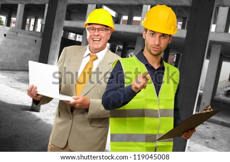 Portrait Of Two Architect Engineers Holding Laptop And Writing Pad, Indoors - stock photo
