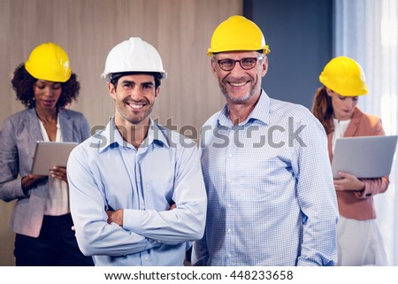 Portrait of two architects standing with arms crossed in office and colleagues working in background