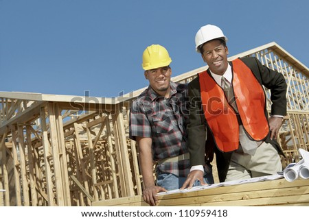 Portrait of two architects with blueprint standing in front of framework at construction site - stock photo