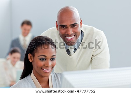 Portrait of two  attractive businesspeople working at a computer in the office