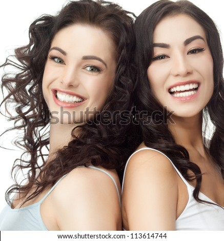portrait of two attractive  caucasian  and asian smiling women brunette isolated on white studio shot - stock photo